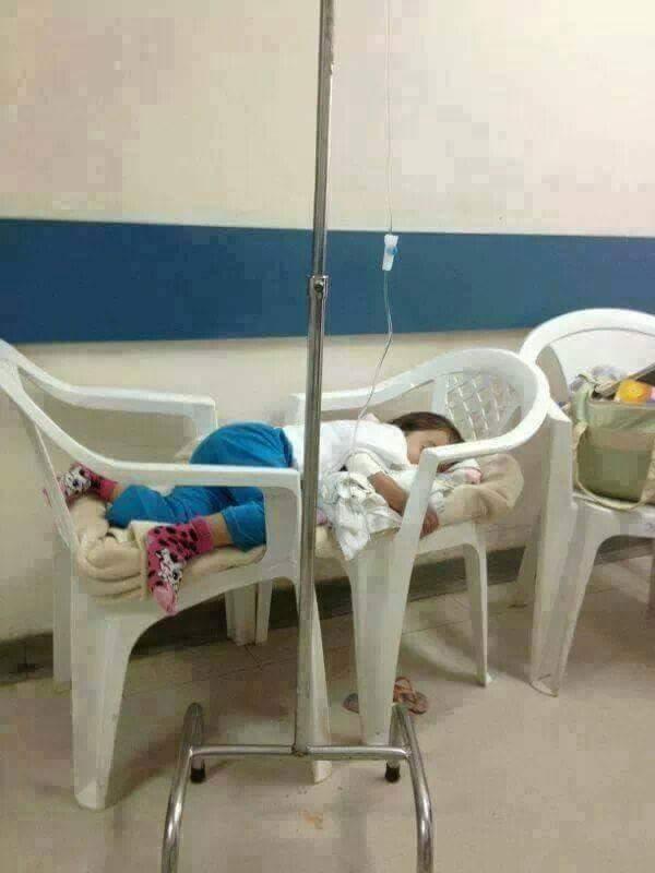 Criança sendo tratada com soro fisiológico em cadeiras improvisando maca.